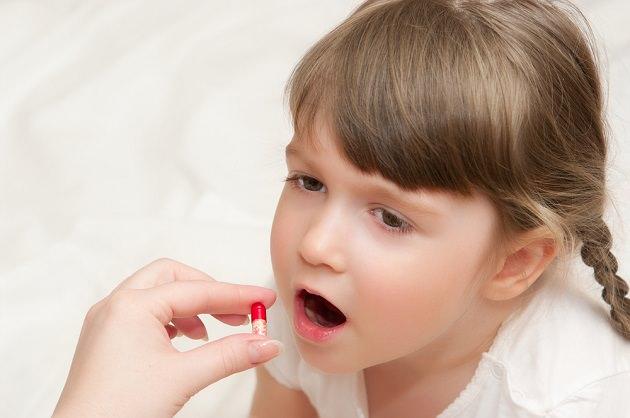 Девочка пьет таблетки