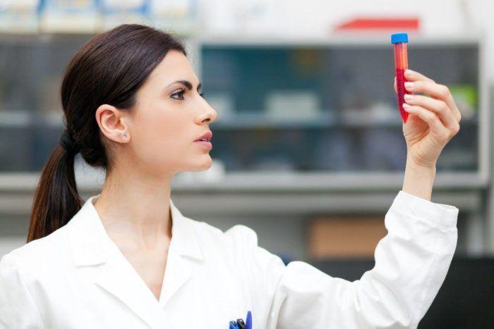 врач смотрит на ампулу с кровью